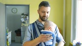 apartament : Young father with his son in sling with smart phone Wideo