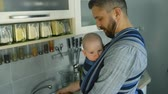 envolto : Young father with his son in sling washing dishes