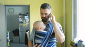 сын : Young father with his son in sling with smart phone Стоковые видеозаписи