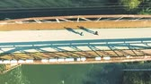 sombra : Runners on rusty bridge above the river . Aerial view.