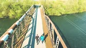 outdoor pursuit : Runners on rusty bridge leading across the river . Aerial view.