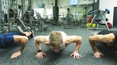push : Three young men in crossfit gym doing push ups. Stock Footage