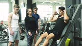 fisiculturismo : Man in gym with personal trainer exercising on leg press machine. Stock Footage