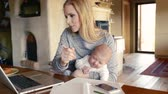 lareira : Beautiful mother with son in the arms, working on laptop Stock Footage