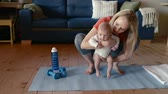 гимнастика : Mother does fitness with her little baby at home.
