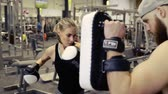 punch : Woman in gym boxing with her personal trainer.