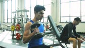 gym : Hispanic man with his friend in gym working out with weights
