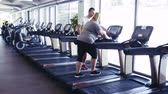 gym : Overweight woman in gym with coach walking on treadmill. Stock Footage
