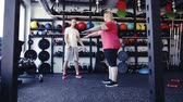 dieta : Overweight woman with personal trainer in modern gym. Vídeos
