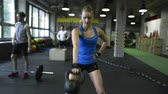 gym : Young fit woman in crossfit gym doing kettlebell swings.
