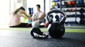 gym : Kettlebells on the floor in gym. Couple stretching legs.