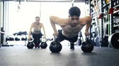 truhe : Junges Fit Paar in der Turnhalle tun Push-ups auf Kettlebells Stock Footage