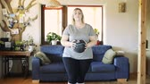 nagy : Attractive overweight woman at home working out with medicine ball.