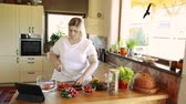 placa de corte : Overweight woman at home preparing vegetable salad in the kitchen.
