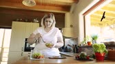 placa de corte : Overweight woman at home eating vegetable salad in the kitchen. Vídeos