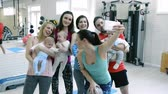 instrutor : Young parents and babies in modern gym taking selfie.