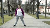 tamanho : Attractive overweight woman in park doing stretching before running.