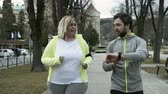 perda de peso : Fitness trainer in town park running with overweight woman. Vídeos