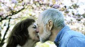 cônjuge : Beautiful senior couple in love outside in spring nature kissing.