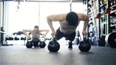 workout : Young fit couple in gym doing push ups on kettlebells