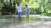 margem do rio : Young father with little boy at the river, sunny spring day.