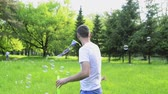 blower : Hipster father and son blowing bubbles outdoors in park.