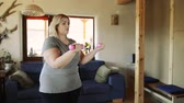 розовый : Attractive overweight woman at home working her biceps with dumbbells.