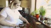 detox : Overweight woman at home preparing vegetable salad in the kitchen.