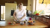 consciente : Attractive overweight woman preparing healthy smoothie.