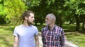 mais velho : Young man and his senior father on a walk in park.