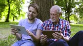vnuk : Young man and his senior father with tablets outdoors. Dostupné videozáznamy