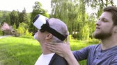 vnuk : Young man and his senior father with VR glasses outdoors. Dostupné videozáznamy