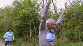 номер : Group of seniors running race in nature on dirt road. Стоковые видеозаписи