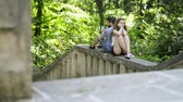 obuv : Young couple with smartphones in town sitting on concrete wall. Dostupné videozáznamy