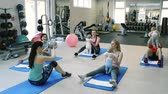 instrutor : Parents exercising with babies in gym with personal trainer.