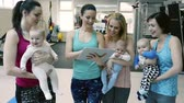 ilerleme : Mothers and babies in gym with personal trainer with tablet.