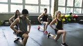 espaçoso : Young people in crossfit gym in lunge position.