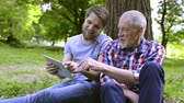 tronco : Young man and his senior father with tablet outdoors.