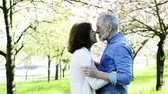 mais velho : Beautiful senior couple in love outside in spring nature kissing.