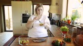 tuk : Overweight woman at home eating vegetable salad in the kitchen. Dostupné videozáznamy