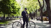 prazer : Mature businessman with smartphone and bicycle in the city.