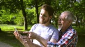 vnuk : Hipster son and his senior father in park taking selfie.