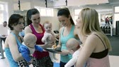 instrutor : Mothers and babies in gym with personal trainer with tablet.