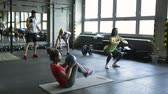 lustro : Young people in crossfit gym working out with various equipment.