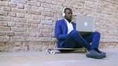 obuv : African businessman with laptop and headphones.