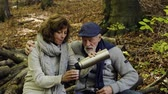 quente : Senior couple on a walk in autumn forest.