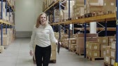 cardboard : Overjoyed female worker or supervisor in a warehouse.