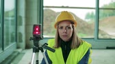 bloco : Young woman worker with laser on the building site.