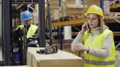 cardboard : Young workers with smartphone and forklift in warehouse. Stock Footage