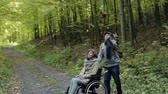 tekerlekli sandalye : Senior couple with wheelchair in autumn forest.